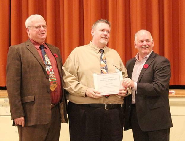Scott Williston and Tim Mifflin presents a certificate of achievement to Bruce Corcoran.