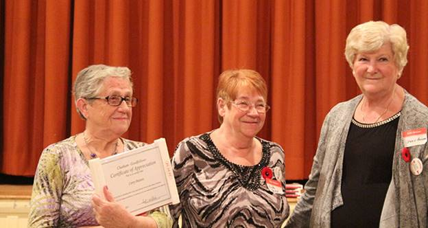 Corry Putters receives a certificate of achievement from Linda Haskell and Judy Bagley.